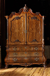 dutch walnut armoire with arched and carved crest above a pair of shaped paneled doors.