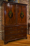 english mahogany linen press with painted oval motif on doors.