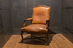 19th century french walnut armchair in the style of a louis xvi. this chair is nicely carved with intricate detail, cabriole legs and tanned leather.