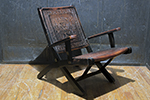 folding leather and wood frame armchair. the leather chair is hand-tooled with a aztec motif.