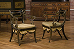regency ebonized beech open armchairs, with sabre legs.