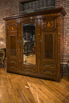 three door wardrobe cabinet with shelving, hanging rods and one mirrored door.
