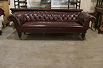 english red leather three seat chesterfield, large scrolled arms, deep buttoned seat the chesterfield is raised on mahogany turned legs with casters.