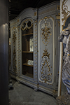 french painted armoire with an arched glazed center door surrounded by two doors with raised gilded